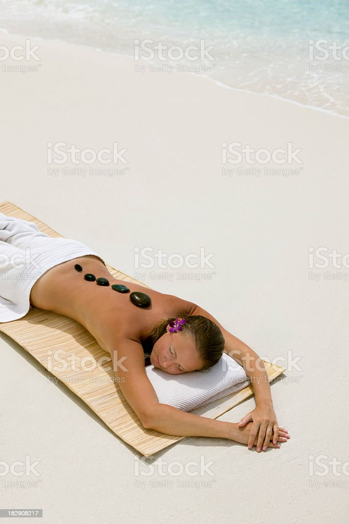 woman getting lastone massage at the beach royalty-free stock photo