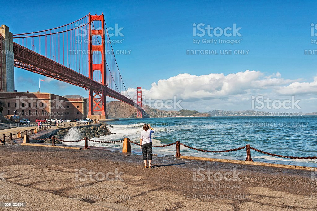 Woman Getting Picture of Golden Gate from Below stock photo
