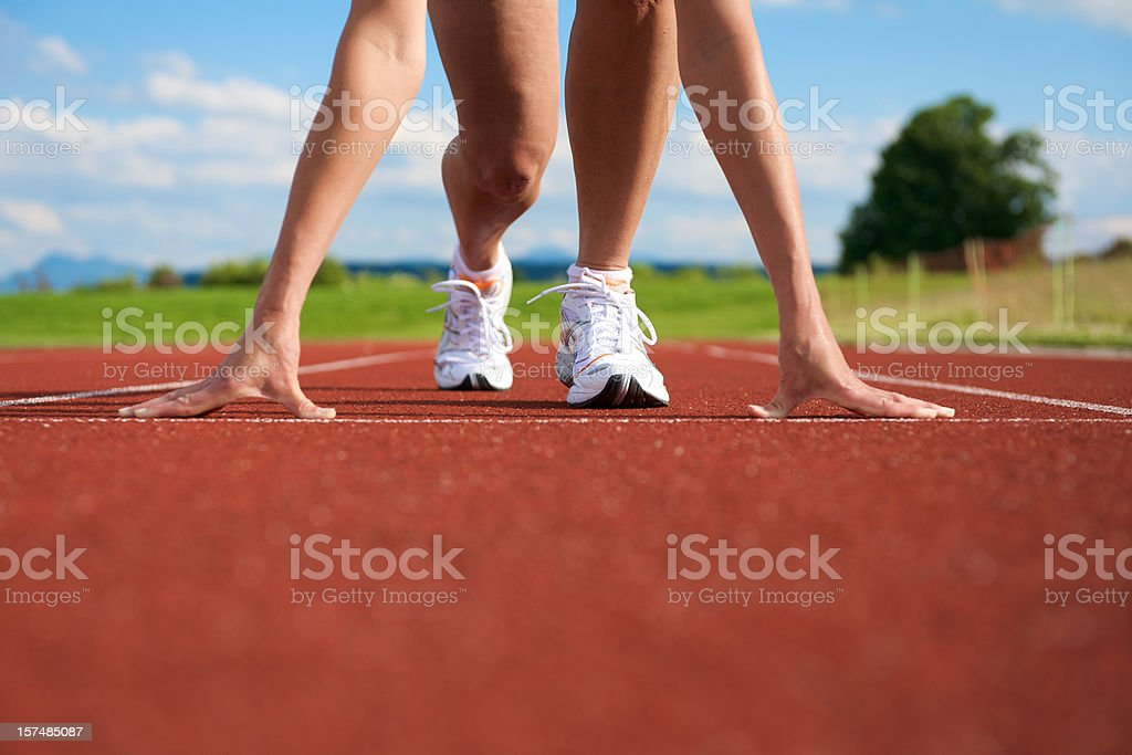 A woman getting ready to sprint on the track and field royalty-free stock photo