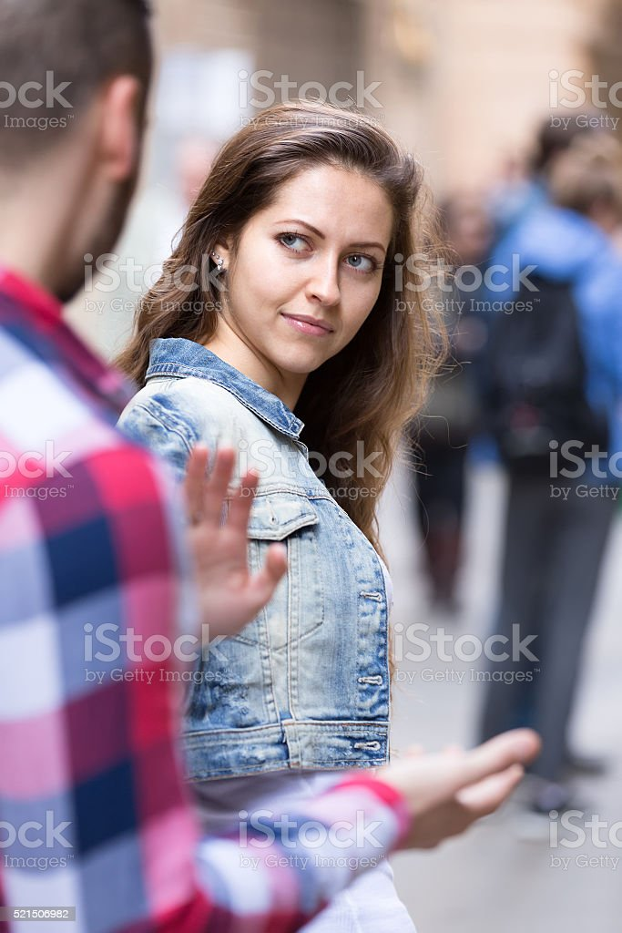 Woman getting rid of stranger on street stock photo