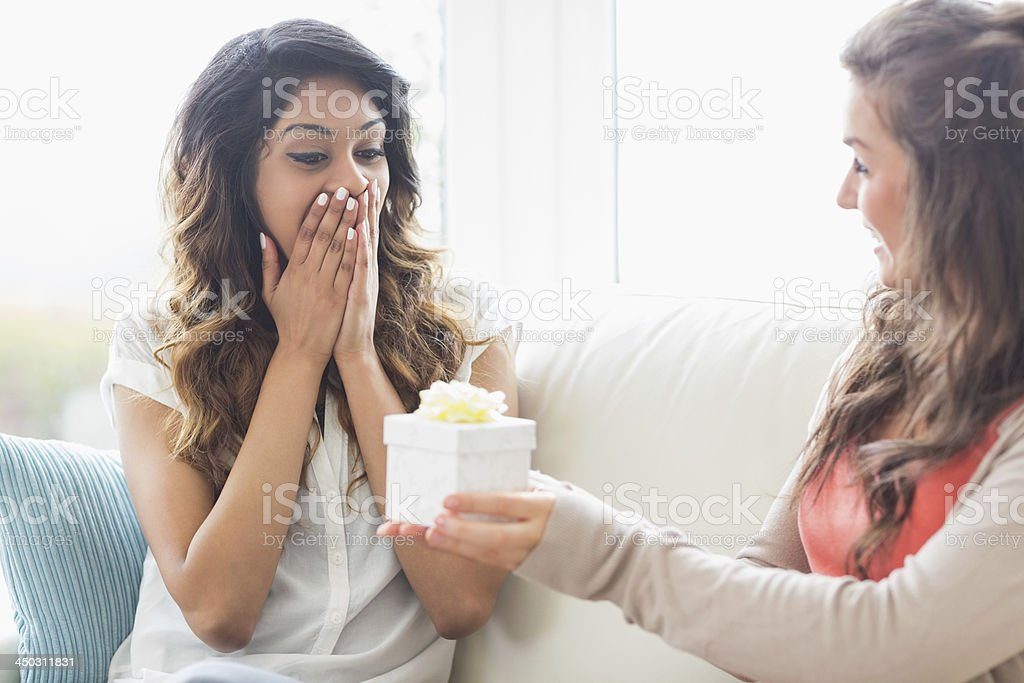 Woman getting surprised by a present stock photo