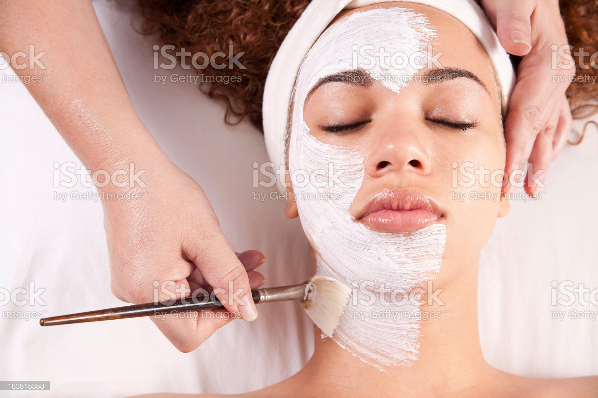 Woman getting white mud painted on her face royalty-free stock photo