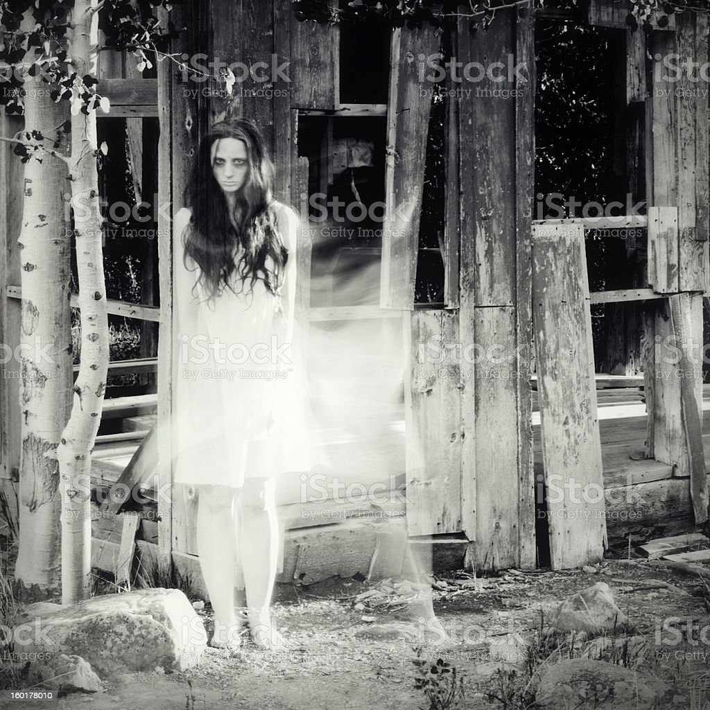 Woman ghost in front of an abandoned house royalty-free stock photo