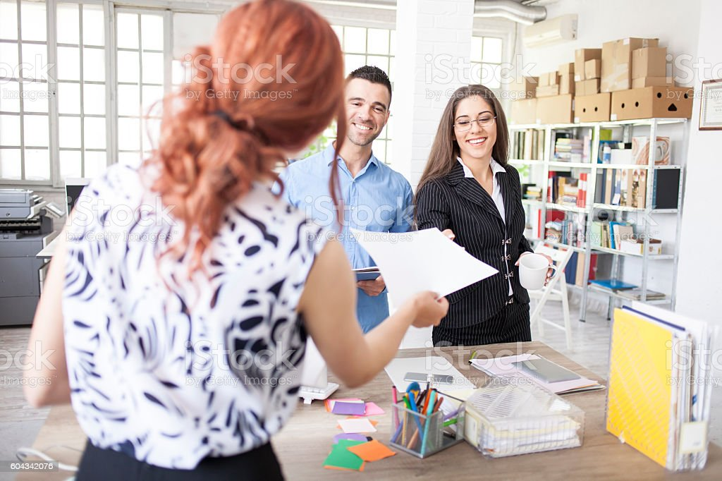 Woman giving an agreement papers to clients stock photo
