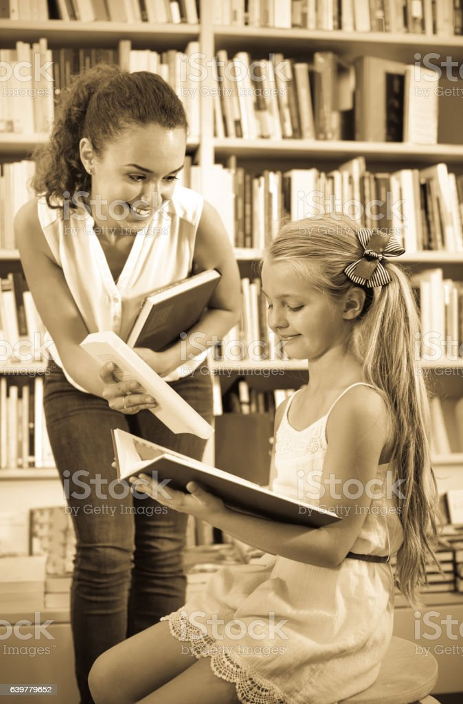 Woman giving book to girl in school age in bookstore stock photo