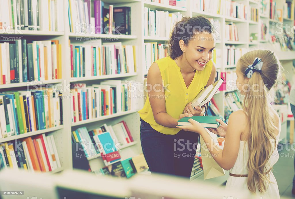 woman giving books to girl in store stock photo