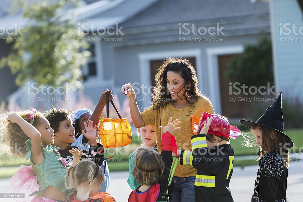 Woman giving candy to children on halloween stock photo