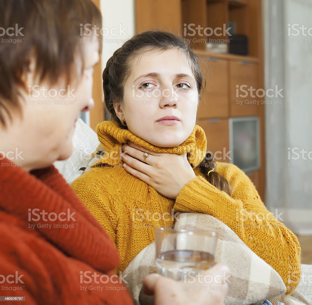 Woman giving glass of water to unwell friend stock photo