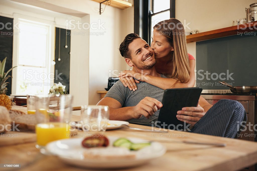 Woman giving good morning kiss to her boyfriend in kitchen stock photo