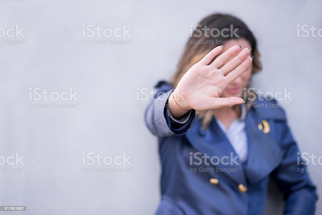 Woman giving hand stop sign while standing against gray wall stock photo