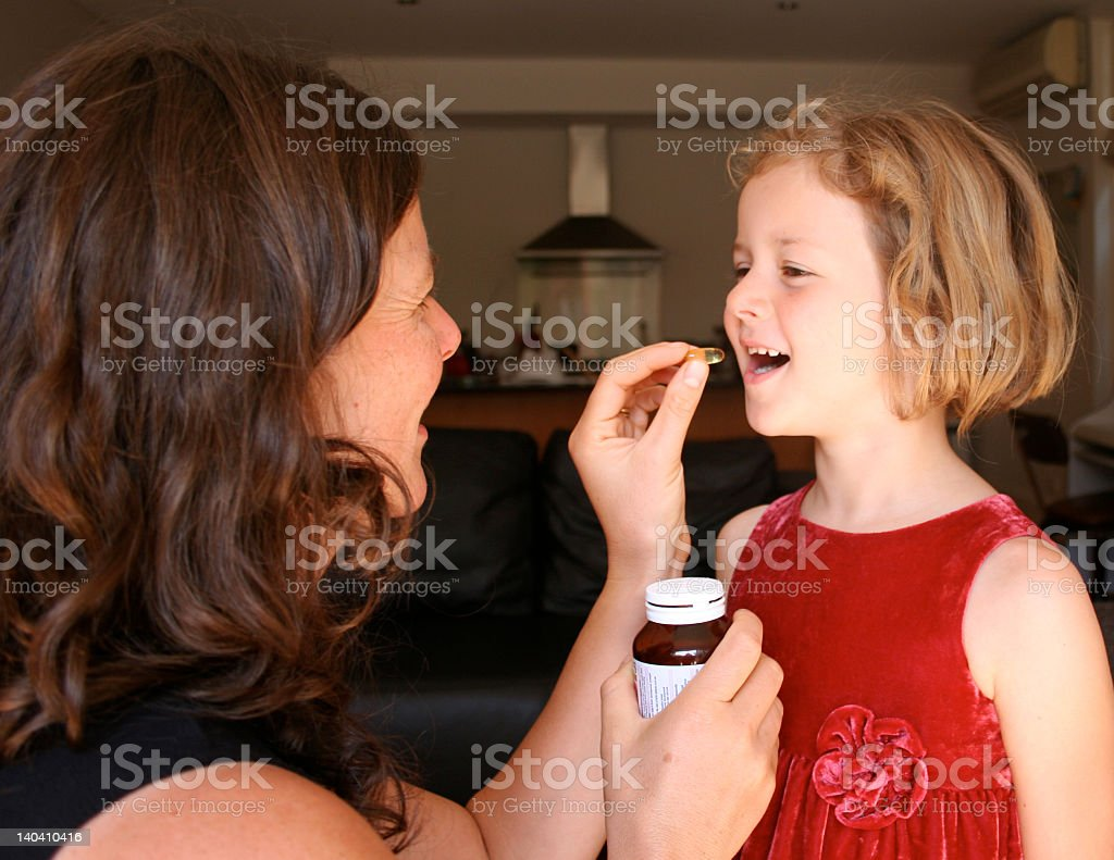 A woman giving her child supplements royalty-free stock photo
