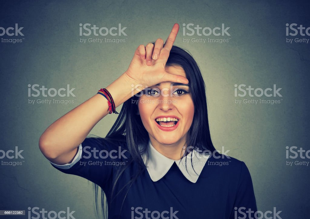 woman giving loser sign looking at you stock photo