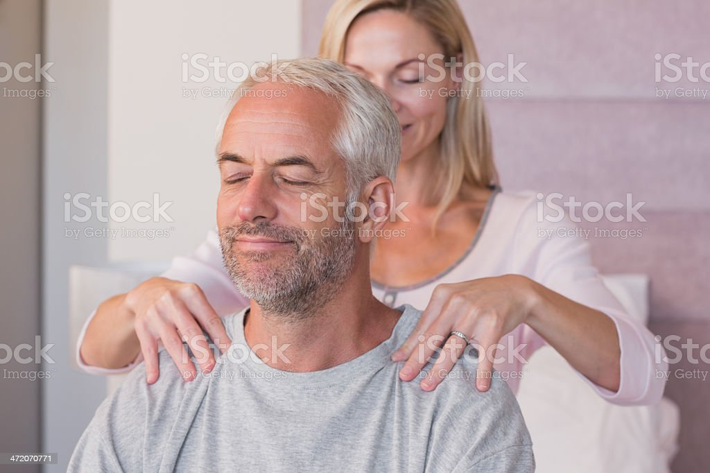 Woman giving massage to her husband royalty-free stock photo