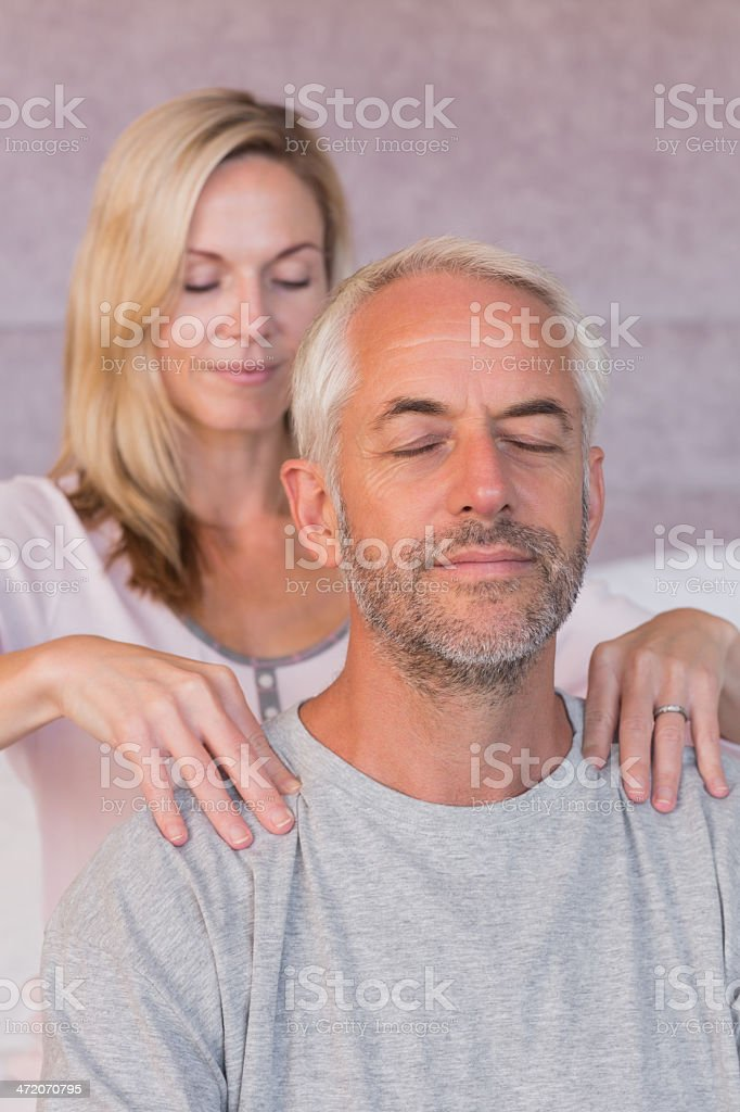 Woman giving massage to her smiling husband royalty-free stock photo