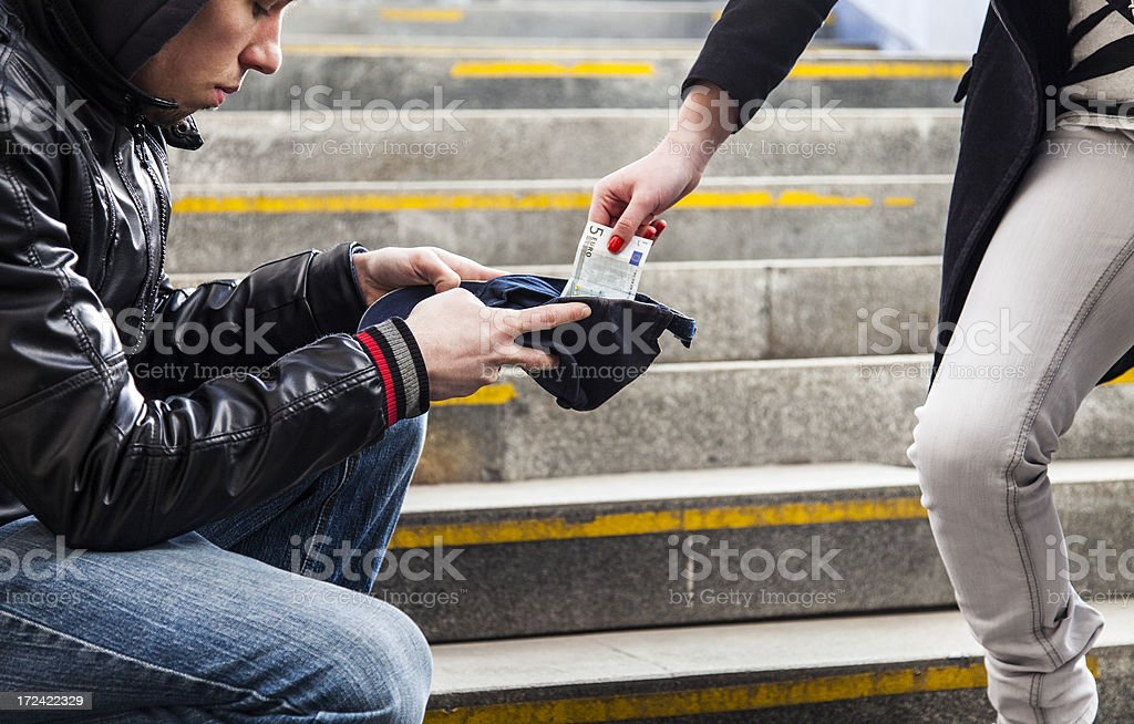 Woman giving money to homeless person royalty-free stock photo