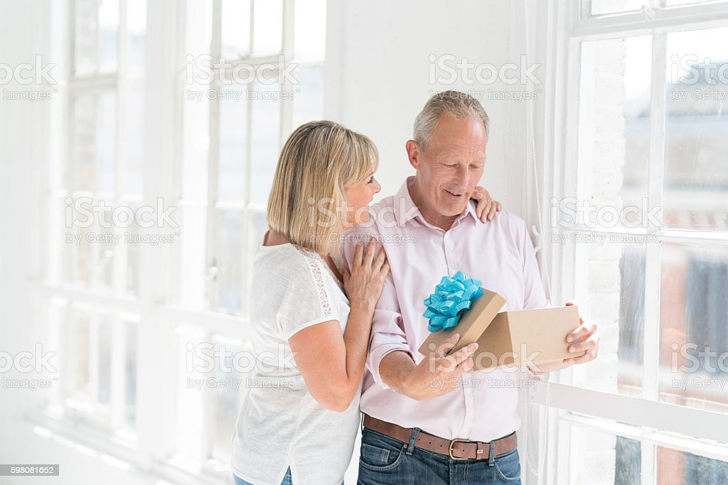 Woman giving present to her husband stock photo