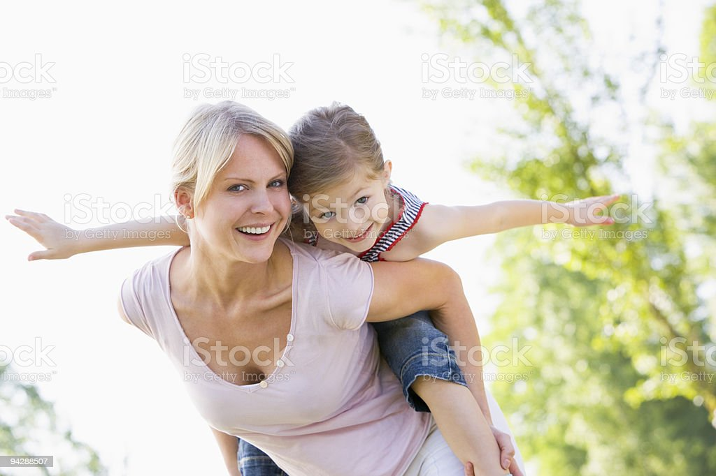 Woman giving young girl piggyback stock photo