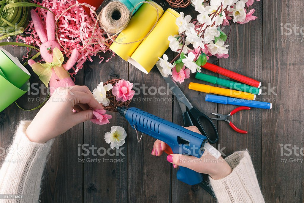 Woman glue handmade flowers with melt gun stock photo