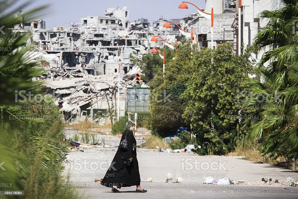 Woman goes near the area destroyed by the fighting stock photo
