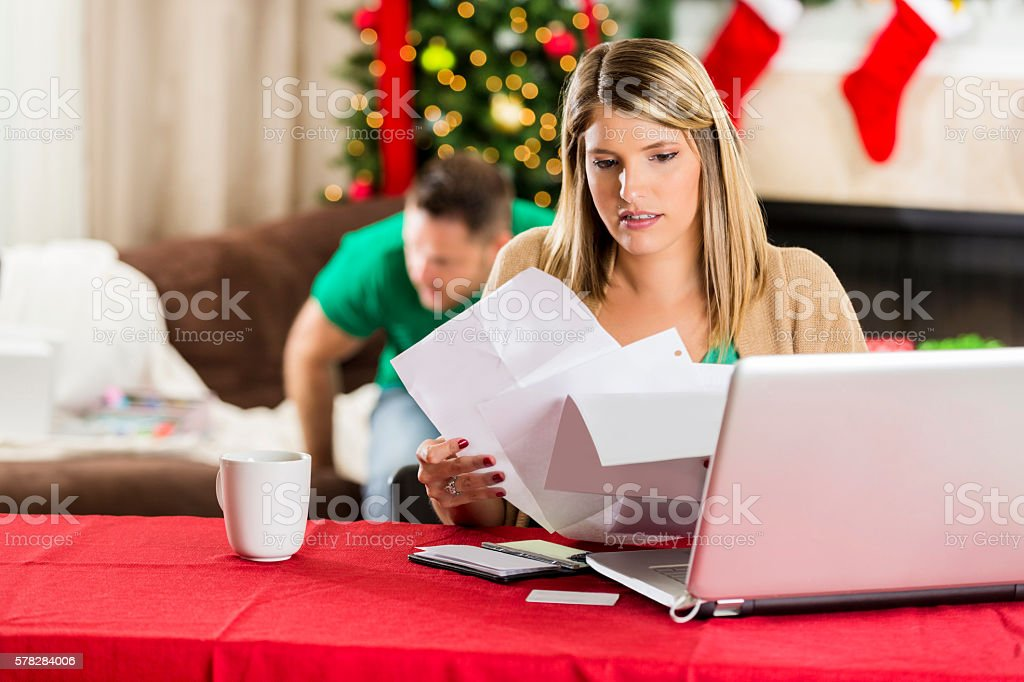 Woman goes through stack of bills during Christmas stock photo