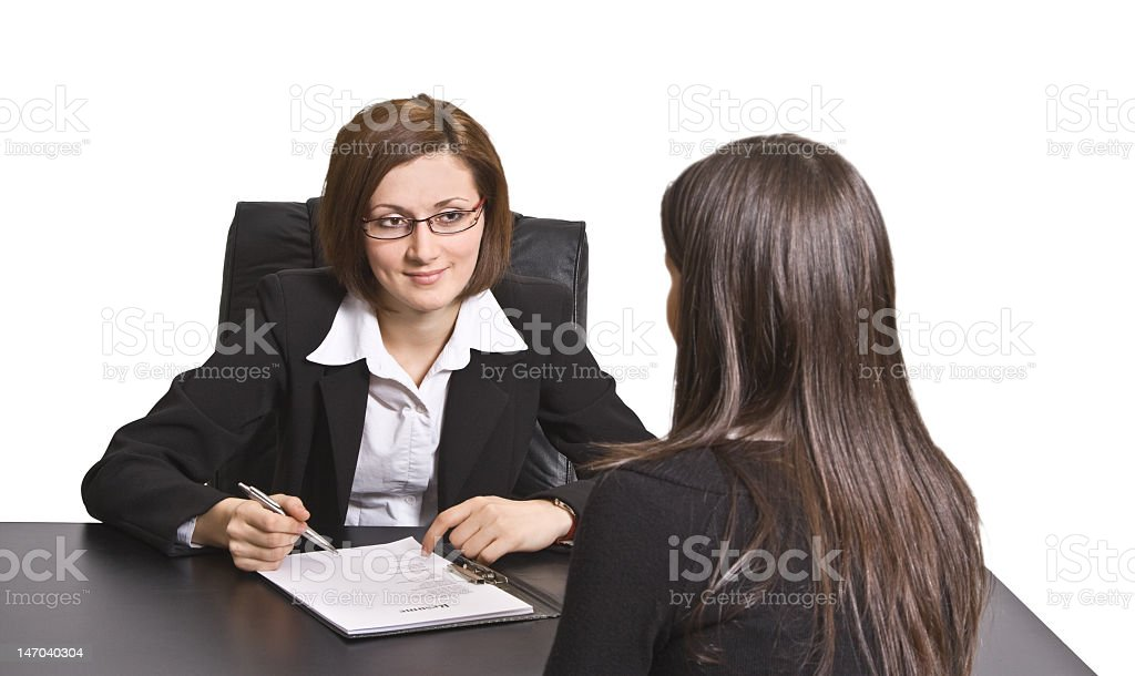 A woman going over paperwork with another woman royalty-free stock photo