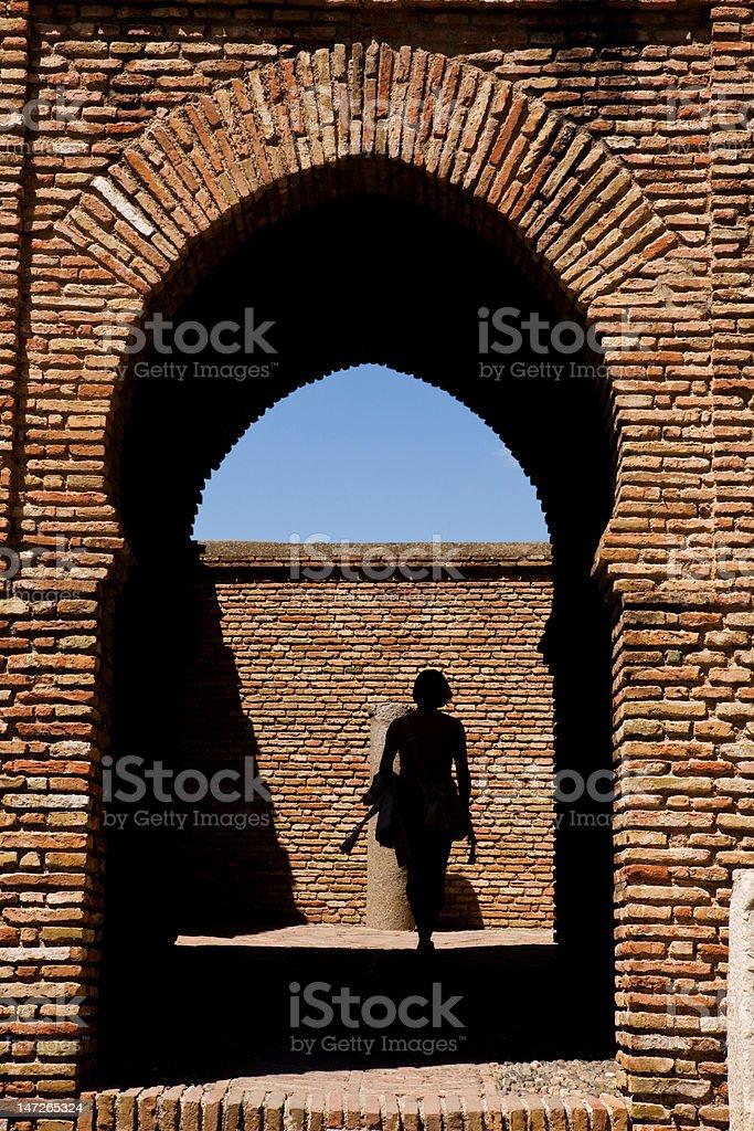 Woman going through the gateway in Alcazaba castle, Malaga royalty-free stock photo