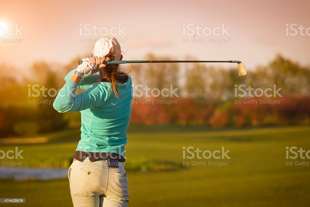 Woman golf player hitting ball. stock photo