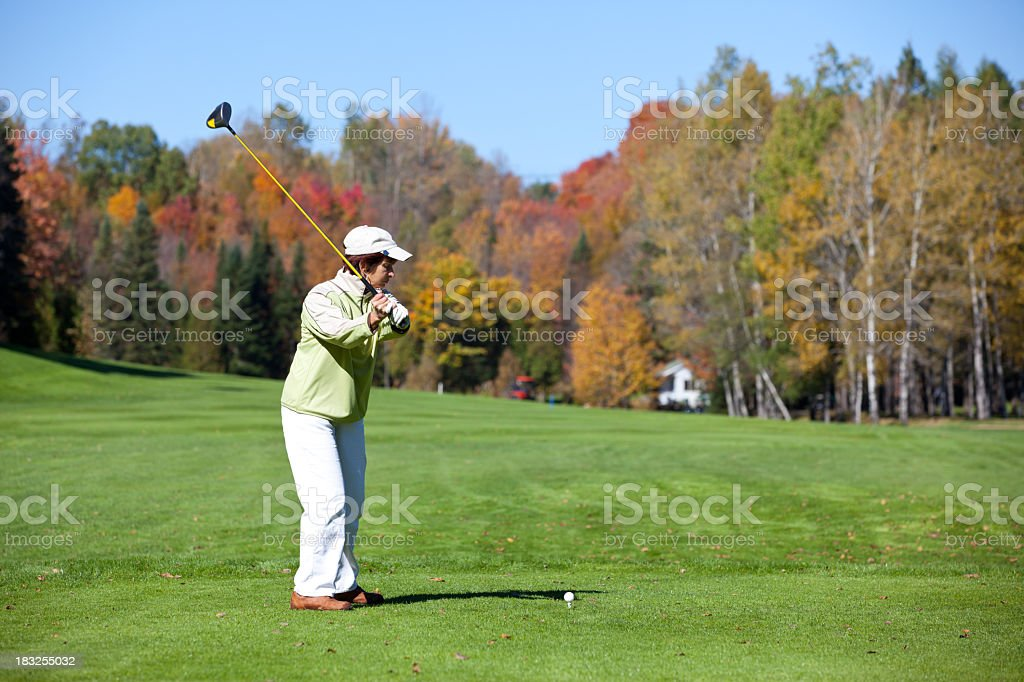 Woman Golf Player in Action in Autumn royalty-free stock photo