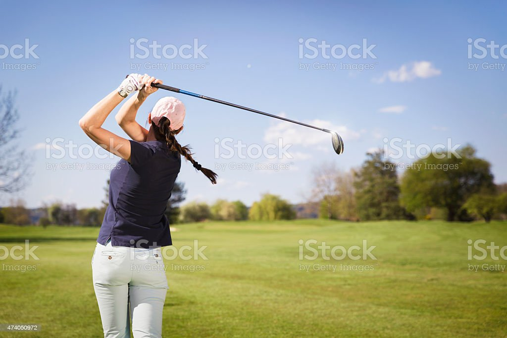 Woman golf player teeing off. stock photo