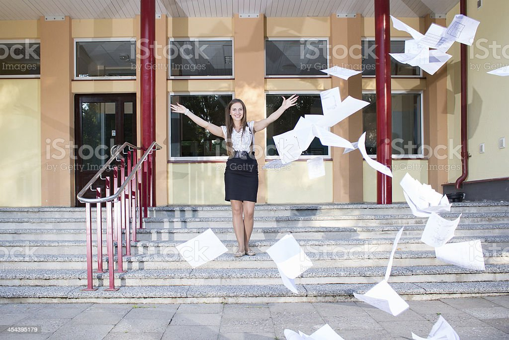 Woman graduates school and discards all her paperwork royalty-free stock photo