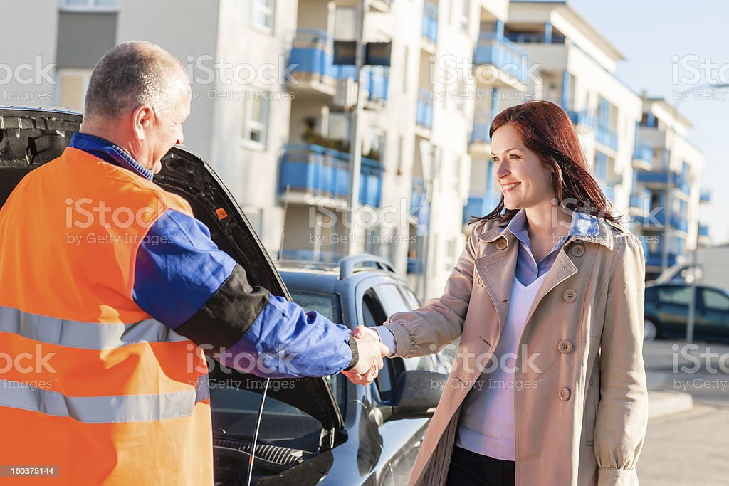 Woman greeting mechanic after her car breakdown royalty-free stock photo