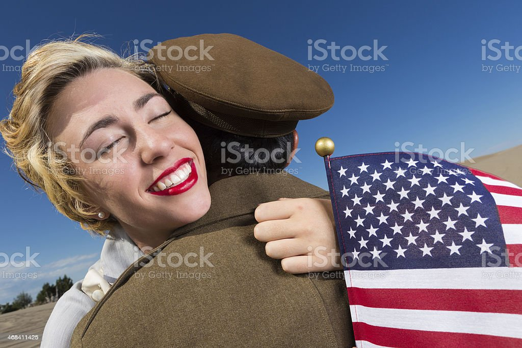 Woman greeting soldier with American flag upon his return royalty-free stock photo