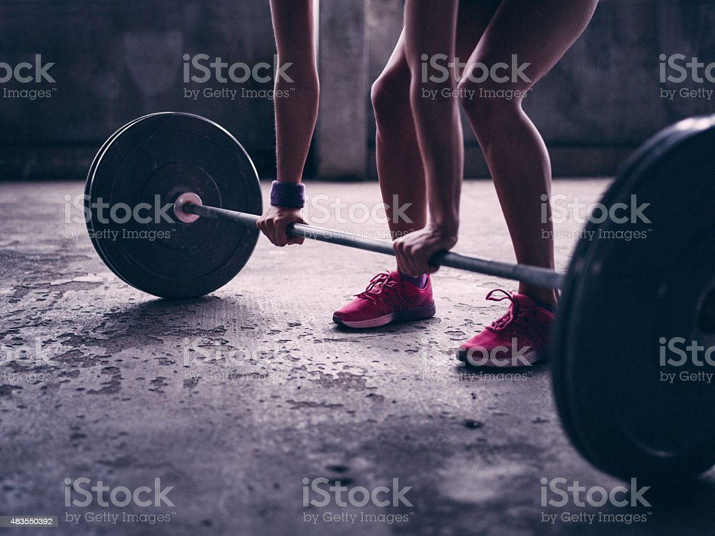 Woman gripping a barbell with heavy weights about to lift stock photo