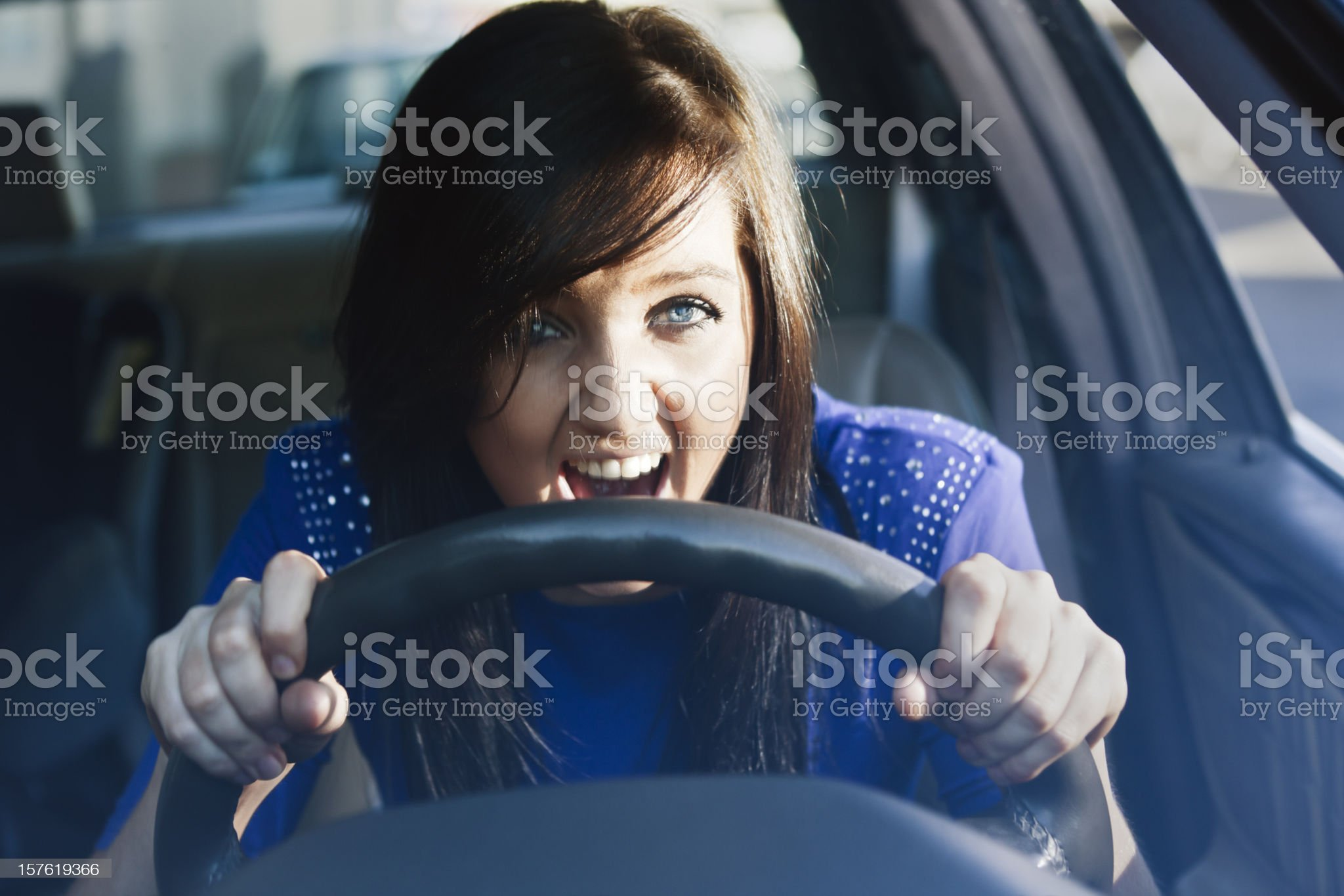 Woman grips steering wheel and yells in fear or frustration royalty-free stock photo