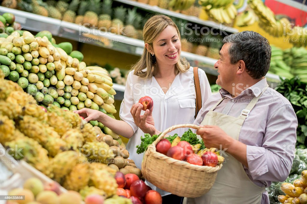 Woman grocery shopping at the food market stock photo