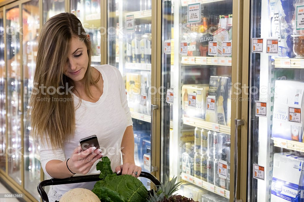 Woman Grocery Shopping with Smart Phone stock photo