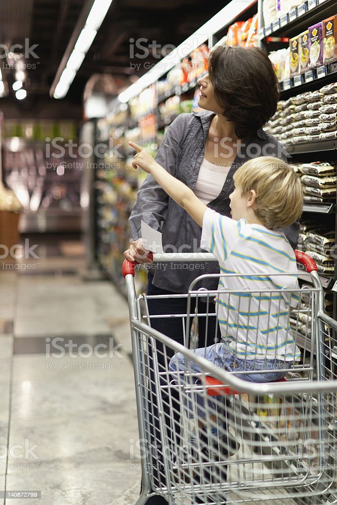 Woman grocery shopping with son stock photo
