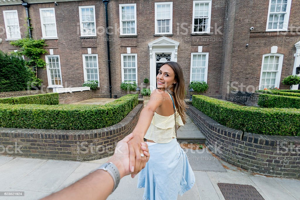 Woman guiding man into their new house stock photo