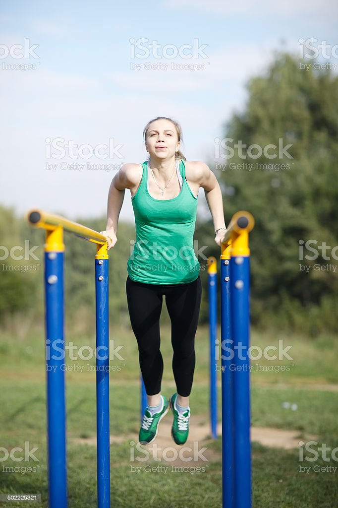 Woman gymnast exercising on parallel bars stock photo