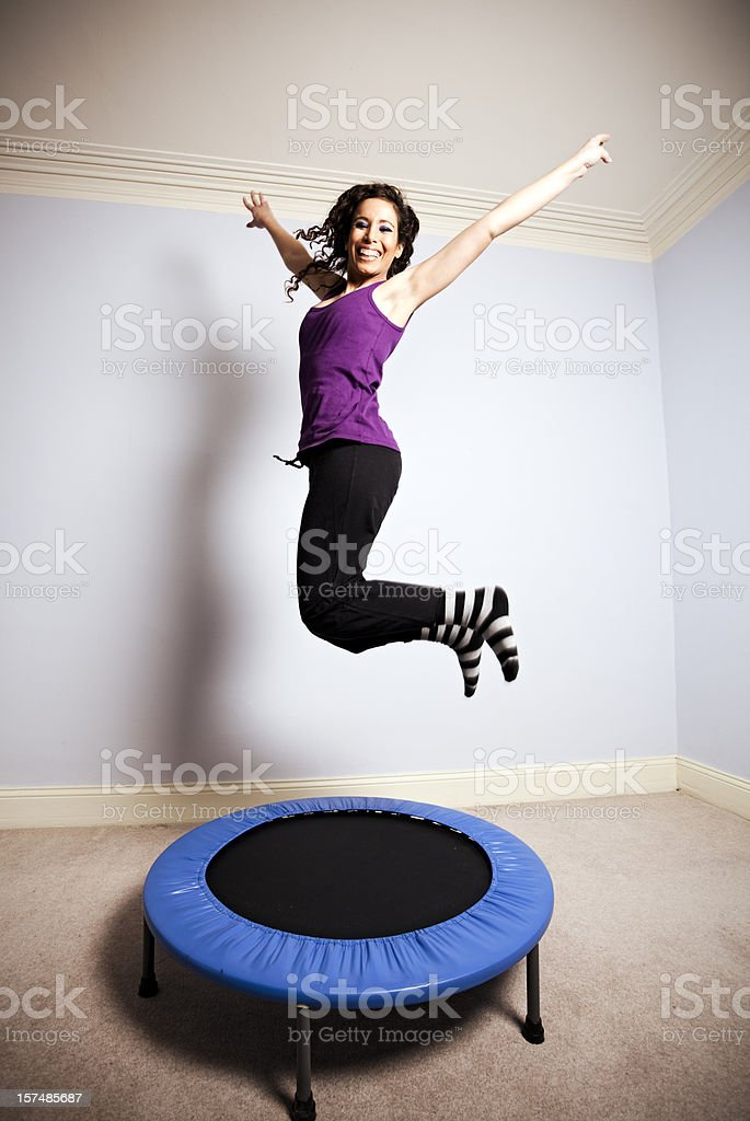 A woman gymnast in mid air above a small trampoline stock photo