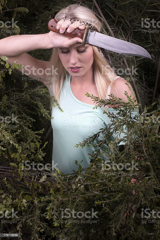 Woman hacking though bushes with big knife royalty-free stock photo