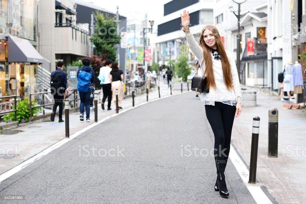 Woman hailing taxi stock photo