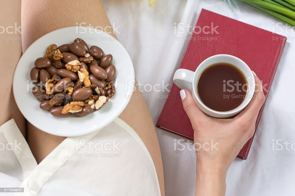 Woman haing a morning snack in bed stock photo
