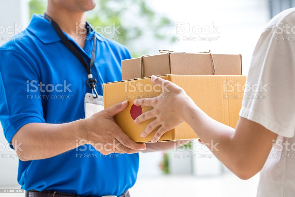 Woman hand accepting a delivery of boxes from deliveryman stock photo