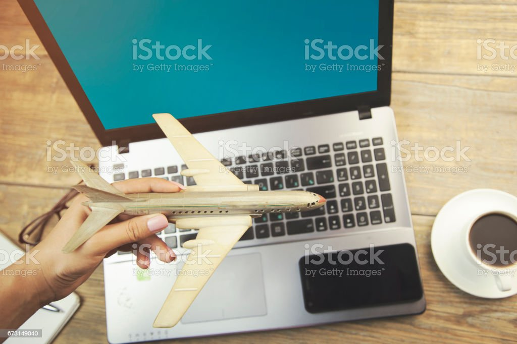 Woman hand airplane and phone on computer keyboard stock photo
