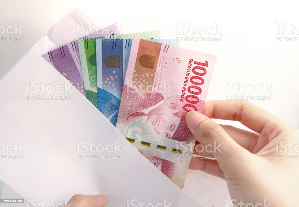 woman hand and Indonesia rupiah money on white envelope stock photo