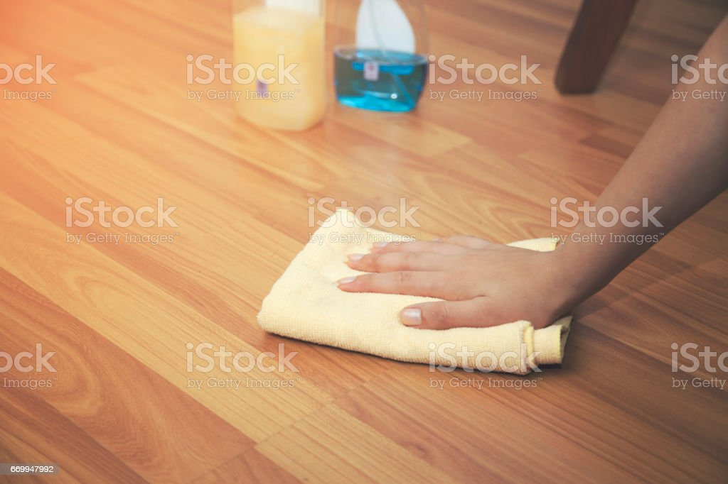 Woman  hand cleaning  an hardwood floor with a microfiber cloth. stock photo