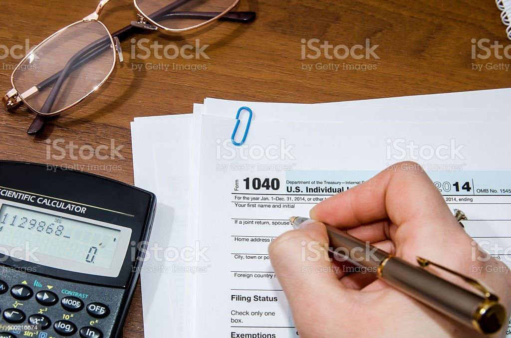 Woman hand filling income tax forms 1040 stock photo