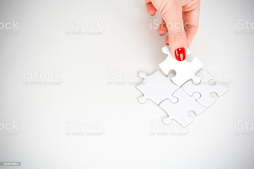 Woman hand fitting the right piece of puzzle stock photo