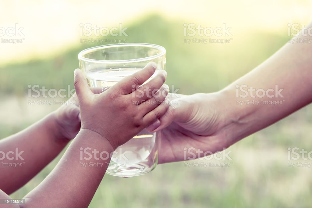 Woman hand giving glass of fresh water to child stock photo